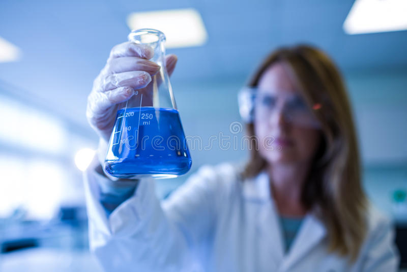 Wissenschaftler, der Becher der Chemikalie hält lizenzfreies stockfoto