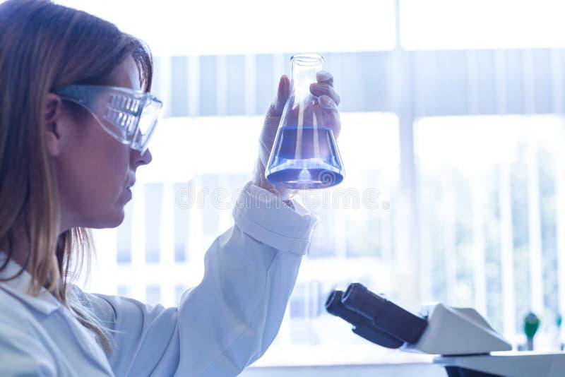 Wissenschaftler, der Becher der Chemikalie hält lizenzfreie stockfotos