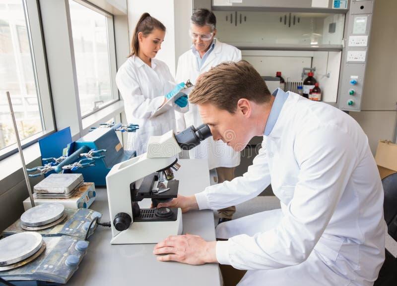 Wissenschaftler, der durch ein Mikroskop schaut stockfotografie