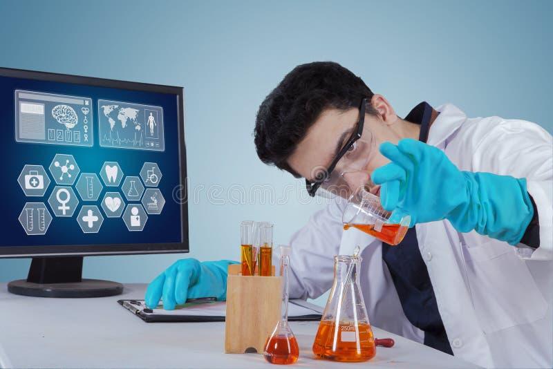 Wissenschaftler, der mit Chemikalie im Labor arbeitet stockfotos