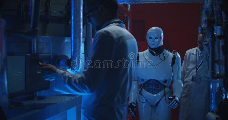 Wissenschaftler, die humanoid Roboter pr?fen lizenzfreie stockfotos