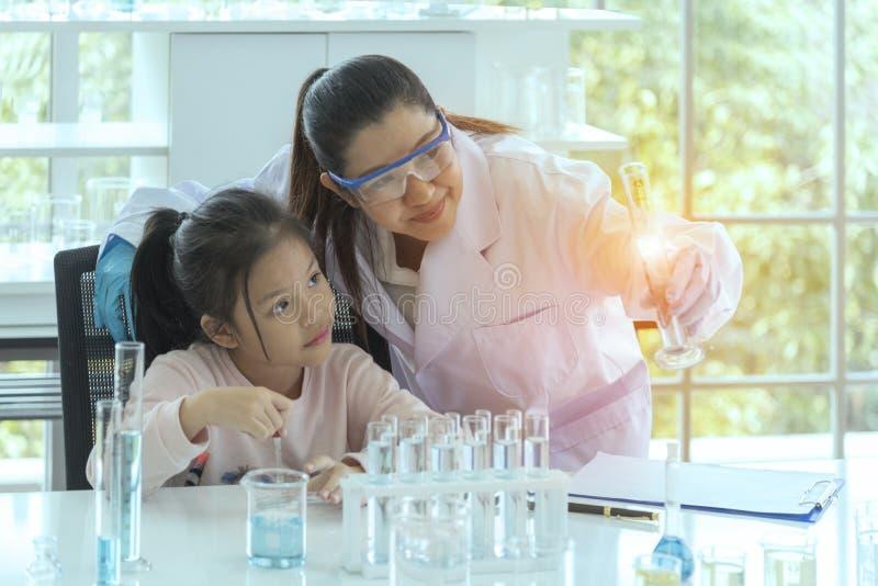 Wissenschaftler erklären das Experiment Der Doktor unterrichtet Mädchen, im Labor zu experimentieren Mädchen, das Wissenschaft st lizenzfreie stockbilder