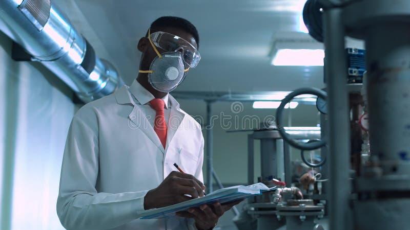 Wissenschaftler im Maskenschreiben im Labor lizenzfreie stockbilder