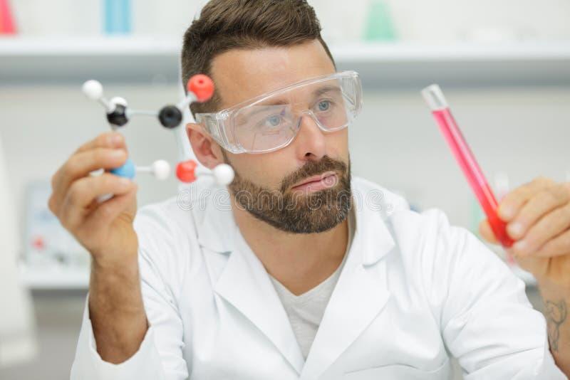 Wissenschaftler mit Reagenzglas und DNA-Molek?l stockfotografie