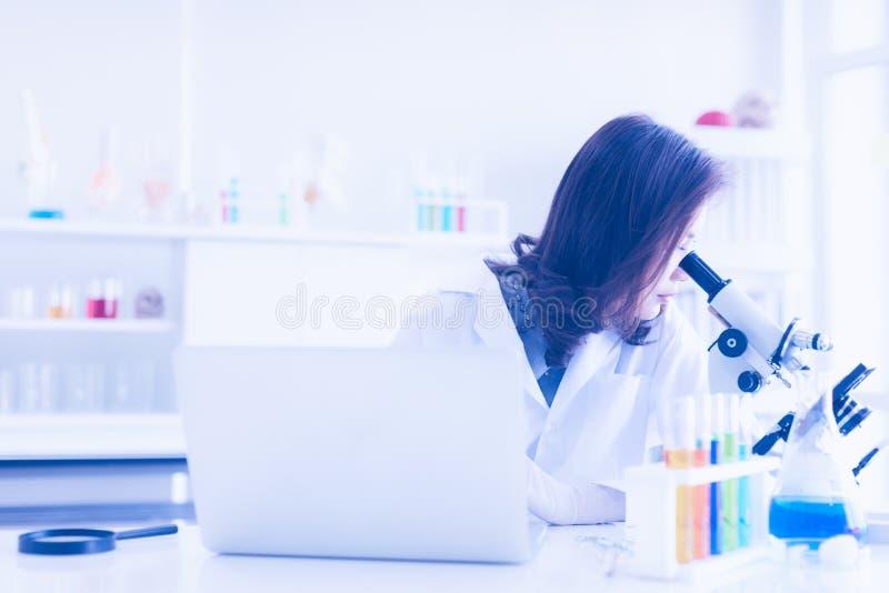 Wissenschaftlerblick durch Mikroskop stockbild