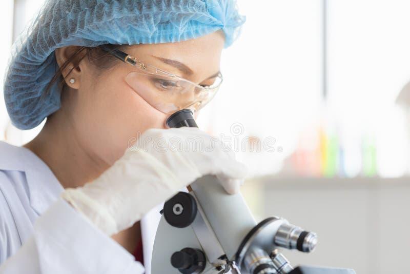Wissenschaftlerblick throgh Mikroskop stockbilder