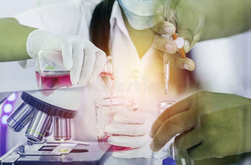 Wissenschaftlerhand mit dem Fallenlassen der chemischen Flüssigkeit mit Forschungs-Chemieflüssigkeit des Wissenschaftlers tragend stockfotos