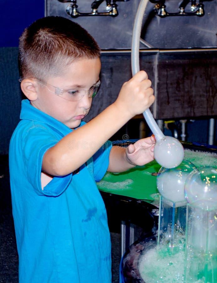 Wissenschaftsexperiment und kleiner Junge stockbild