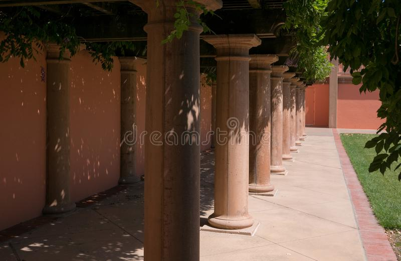 Wisteria shades a walkway. Napa Valley winery architecture, shaded walkway under Wisteria canopy royalty free stock photos