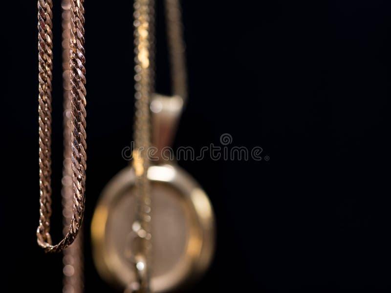 Wiszący istni złoto łańcuchy w rzędzie, złoty medal w zamazanym tle odizolowywającym na czerni fotografia stock