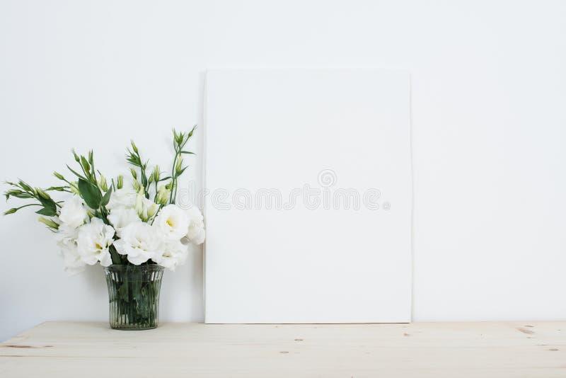 Wit binnenlands decor, verse natuurlijke bloemen in vaas en canvas stock foto