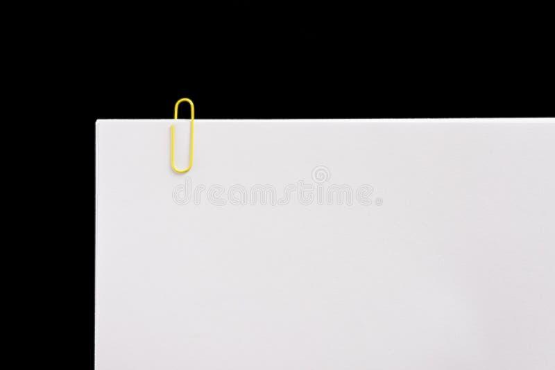 Wit blad met klemmen op zwarte achtergrond royalty-vrije stock foto