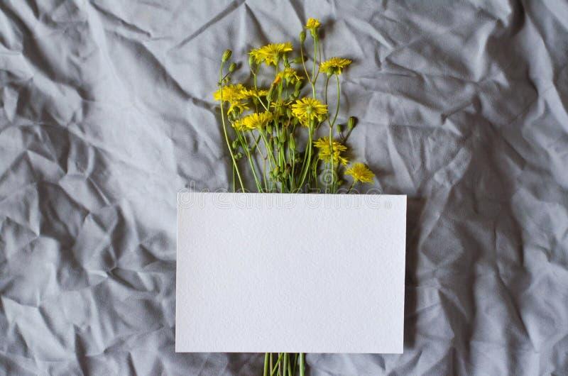 Wit blad op een grijze stoffenachtergrond met gele bloemen royalty-vrije stock afbeeldingen