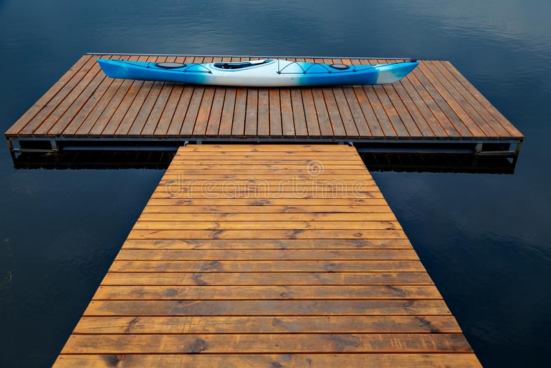 Wit-blauwe plastic kajak die op een houten dok liggen stock foto