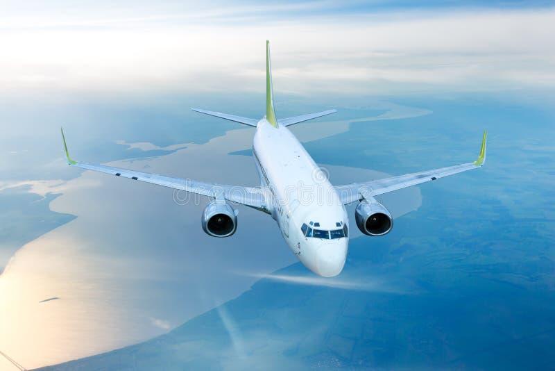 Wit burgerlijk vliegtuig in de hemel stock foto's