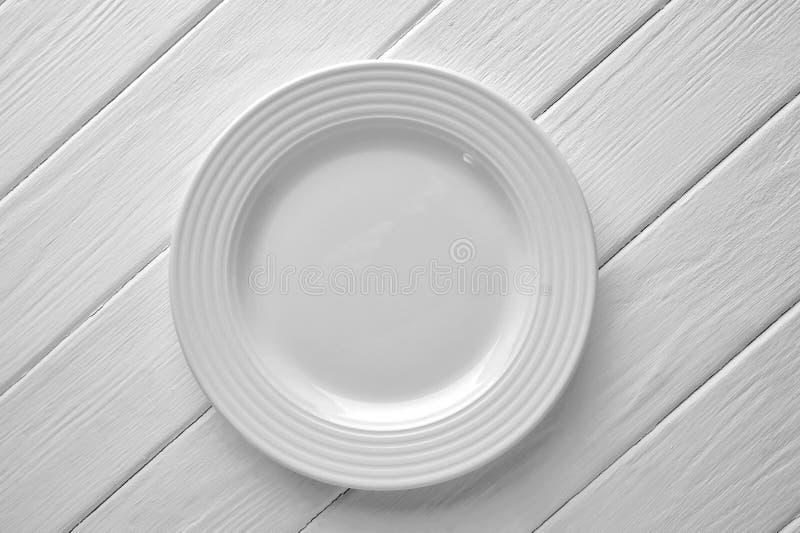 Wit ceramisch plaatclose-up op geschilderde houten achtergrond stock foto