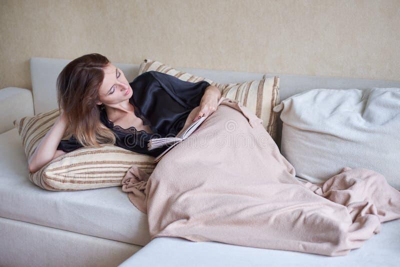 Wit comfortabel bed en een mooi meisje, die een boek, concepten lezen huis en comfort stock foto's