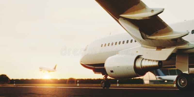 Wit commercieel vliegtuig die zich op de luchthavenbaan bij zonsondergang bevinden Het passagiersvliegtuig stijgt op stock afbeelding
