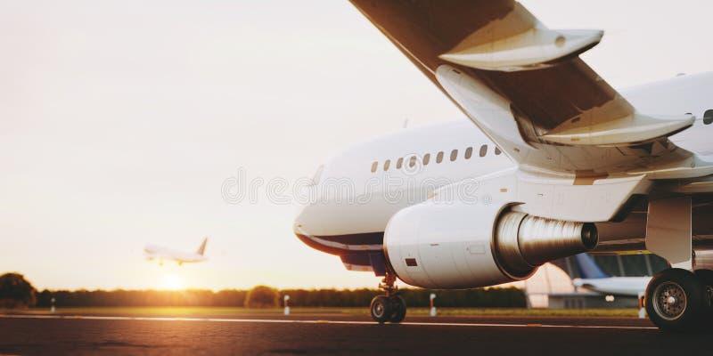 Wit commercieel vliegtuig die zich op de luchthavenbaan bij zonsondergang bevinden Het passagiersvliegtuig stijgt op stock foto