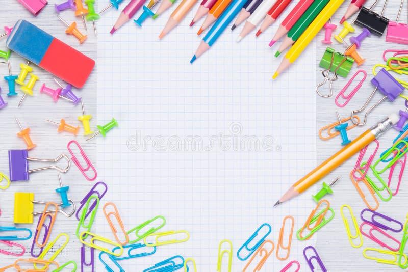 Wit die bladnotitieboekje, door kleurrijke kantoorbehoeftenpunten wordt omringd, paperclippen, knopen, potloden royalty-vrije stock foto