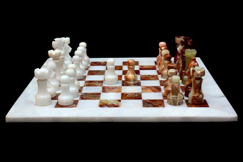 Wit die marmer en onyxsteenschaakbord met stukken, op zwarte achtergrond worden geïsoleerd stock afbeelding
