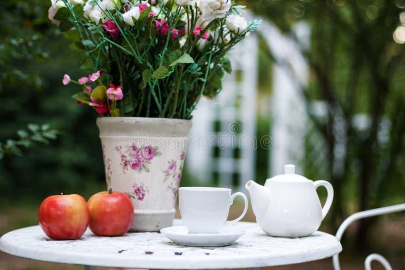 Wit die porselein voor thee of koffie op lijst in de tuin over achtergrond van de onduidelijk beeld de groene aard, ondiepe diept royalty-vrije stock afbeelding