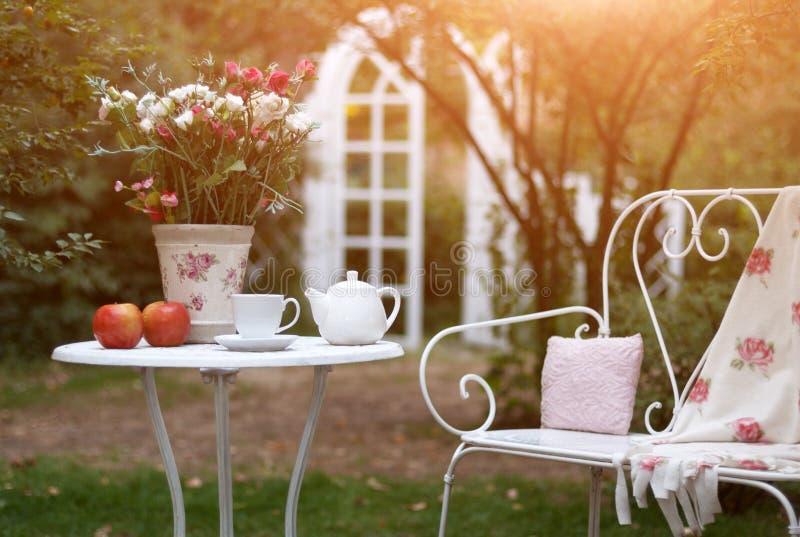 Wit die porselein voor thee of koffie op lijst in de tuin over achtergrond van de onduidelijk beeld de groene aard wordt geplaats royalty-vrije stock afbeelding