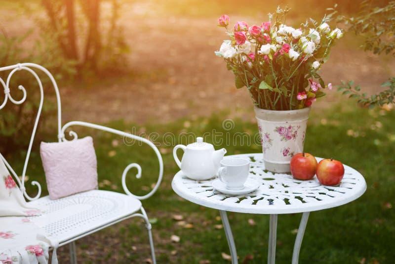 Wit die porselein voor thee of koffie op lijst in de tuin over achtergrond van de onduidelijk beeld de groene aard wordt geplaats royalty-vrije stock foto