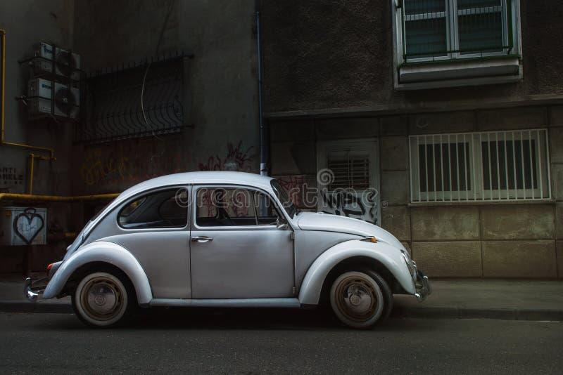 Wit die Volkswagen Beetle in het midden van de stad wordt geparkeerd royalty-vrije stock fotografie