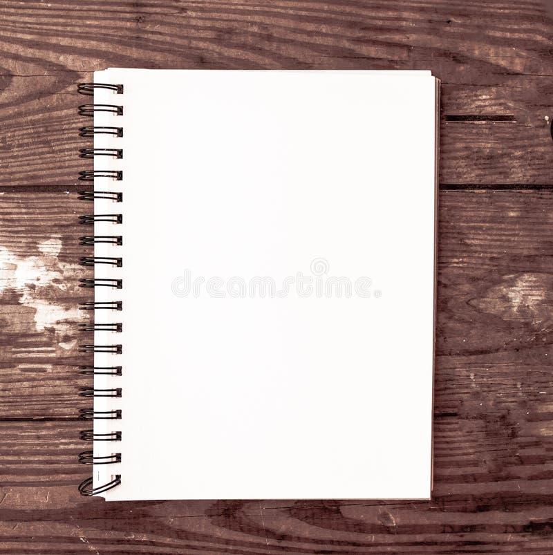 wit duidelijk notitieboekje voor sociale media die post met houten achtergrond op de markt brengen stock foto
