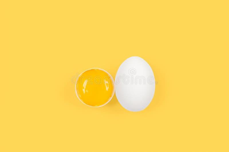 Wit ei en dooier Ruwe eieren op pastelkleur gele achtergrond stock afbeelding