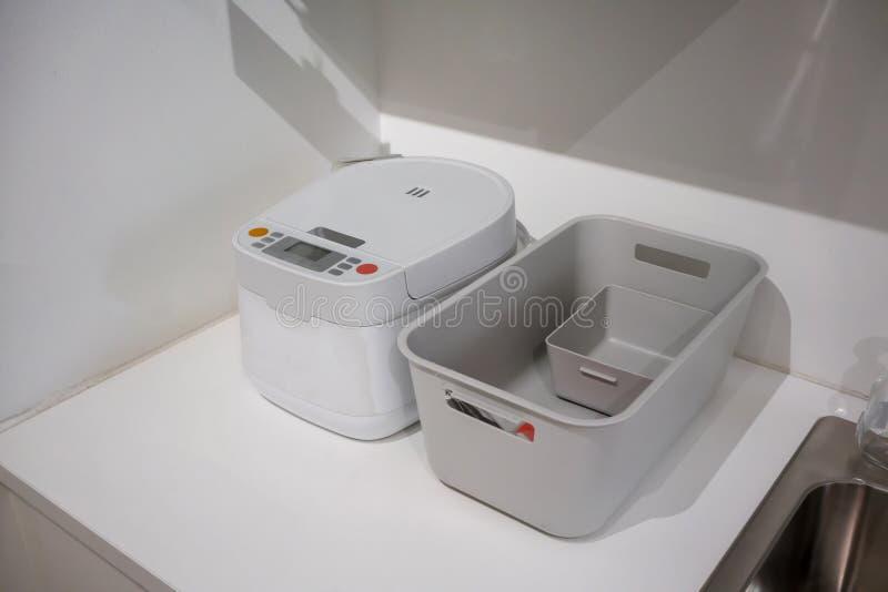 Wit elektrisch rijstkooktoestel en grijze plastic mand op keukensi royalty-vrije stock afbeeldingen