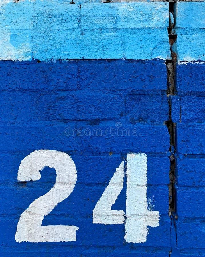 Wit gestencild nummer vierentwintig op muur stock afbeeldingen