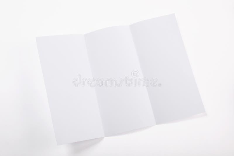 Wit gevouwen die document blad op witte achtergrond met exemplaarruimte wordt geïsoleerd stock fotografie