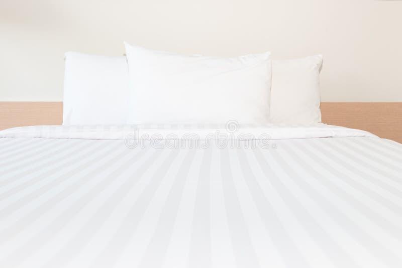Wit hoofdkussen en wit bed in bedruimte stock afbeelding