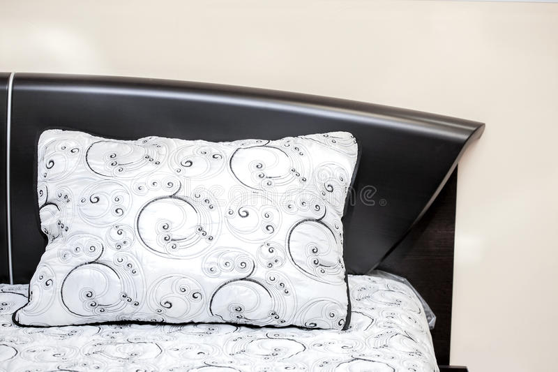 Wit hoofdkussen met zwarte geborduurde patronen op een krachtig bed van ebbehouten slaapkamerbinnenland royalty-vrije stock foto's
