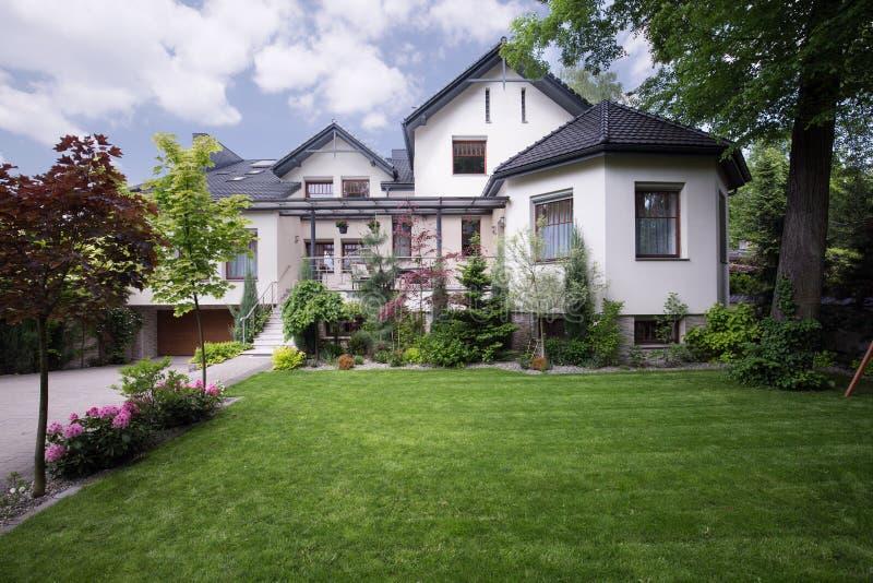 Wit huis met voorwerf stock fotografie
