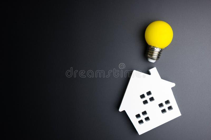 Wit huisstuk speelgoed en gloeilamp op zwarte achtergrond met exemplaarkuuroord stock fotografie