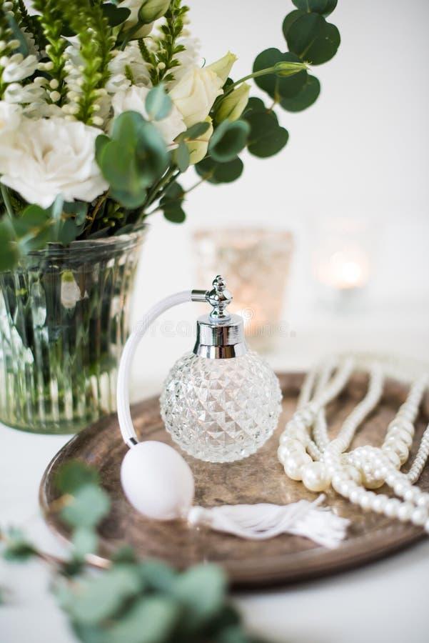 Wit huwelijksdecor, parfum, parelparels en boeket van bloemen stock foto