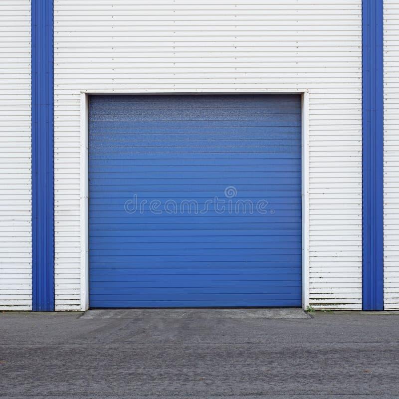 Wit Industrieel pakhuis met blauwe deur voor vrachtwagens royalty-vrije stock foto's