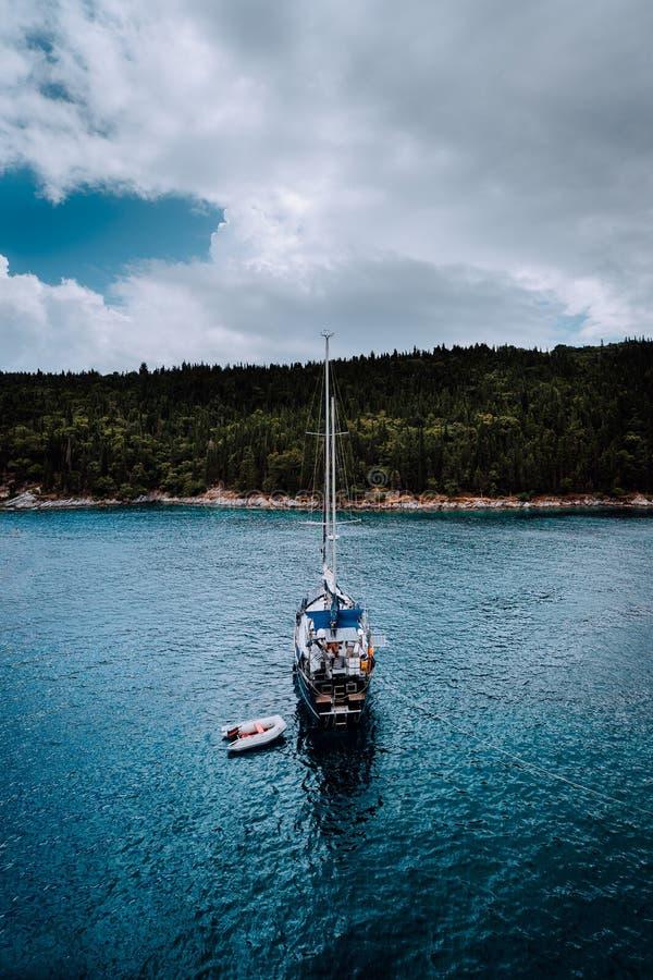 Wit Jacht dat in kalme baai vaart dichtbij aan Griekse kust Dramatisch onweer cloudscape Donkere dag, donkere schaduwen van wolke royalty-vrije stock afbeeldingen