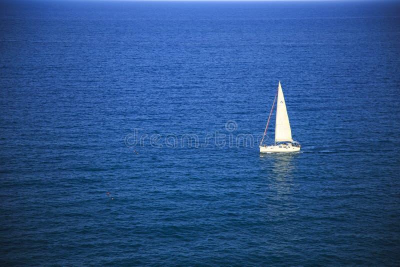 Wit jacht in een diepe blauwe overzees stock afbeeldingen