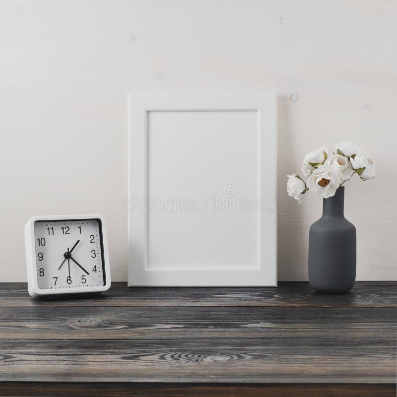 Wit kader, bloem in vaze, klok op donkergrijze houten lijst tegen de witte muur met exemplaarruimte Spot omhoog stock afbeeldingen
