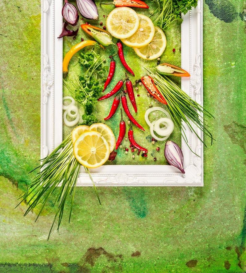 Wit kader met verse kruiden, Spaanse peper, tuinkruiden en citroen op groene achtergrond, hoogste mening stock afbeeldingen