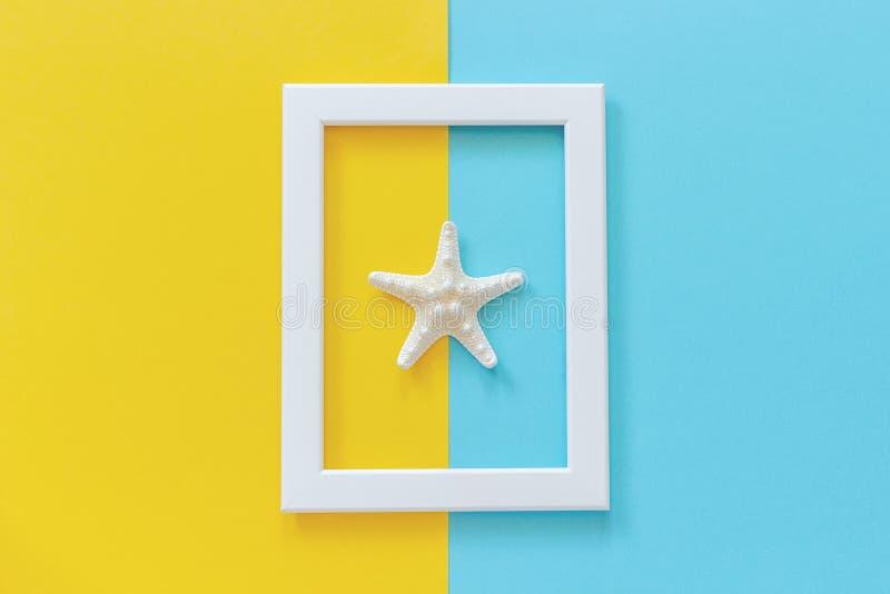 Wit kader met zeester op blauwe en gele achtergrond De creatieve Vlakte legt Hoogste meningsmalplaatje voor prentbriefkaar, de ru royalty-vrije stock foto