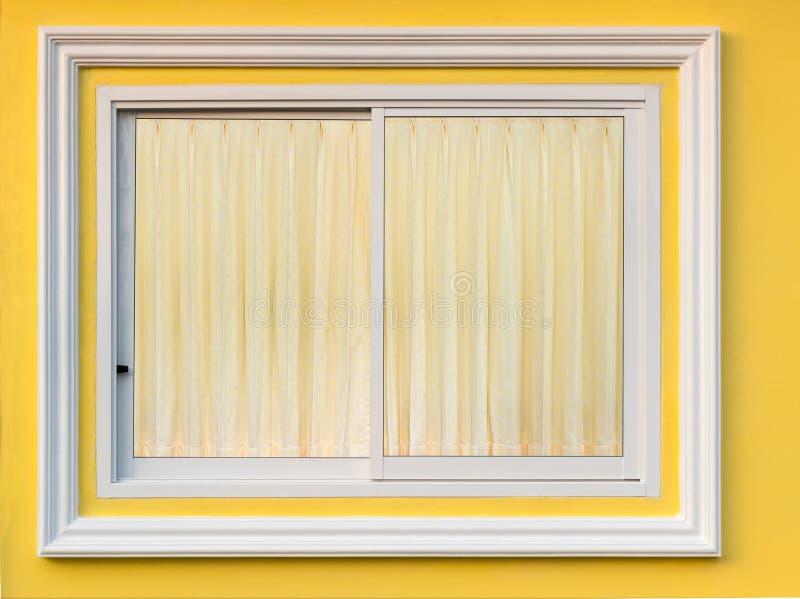 Wit kadervenster in gele muur met gordijn royalty-vrije stock afbeeldingen