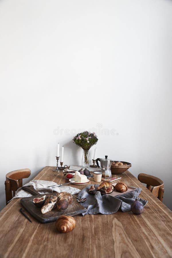 Wit keukenbinnenland met het ontbijt van de Provence op houten lijst, lege witte muur, daglicht stock foto