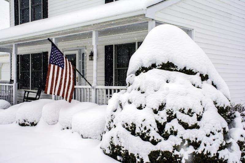 Wit koloniaal huis in sneeuwonweer stock afbeeldingen