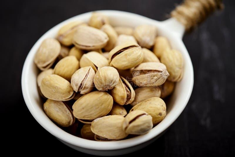 Wit komhoogtepunt van heerlijke pistaches op een oude zwarte lijst stock afbeeldingen