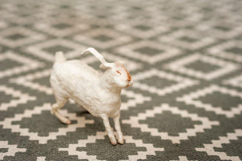 Wit konijntje op een weefselachtergrond van een tapijt met een geometrisch patroon Pasen-concept, tederheid, uniciteit, schoonhei royalty-vrije stock afbeelding